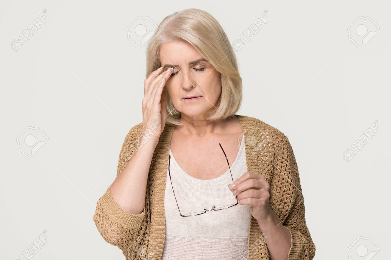 Upset tired old mature woman taking off glasses feeling eyestrain pain, stressed aged senior lady suffer from headache bad vision eye strain fatigue problem isolated on grey white studio background - 118048276