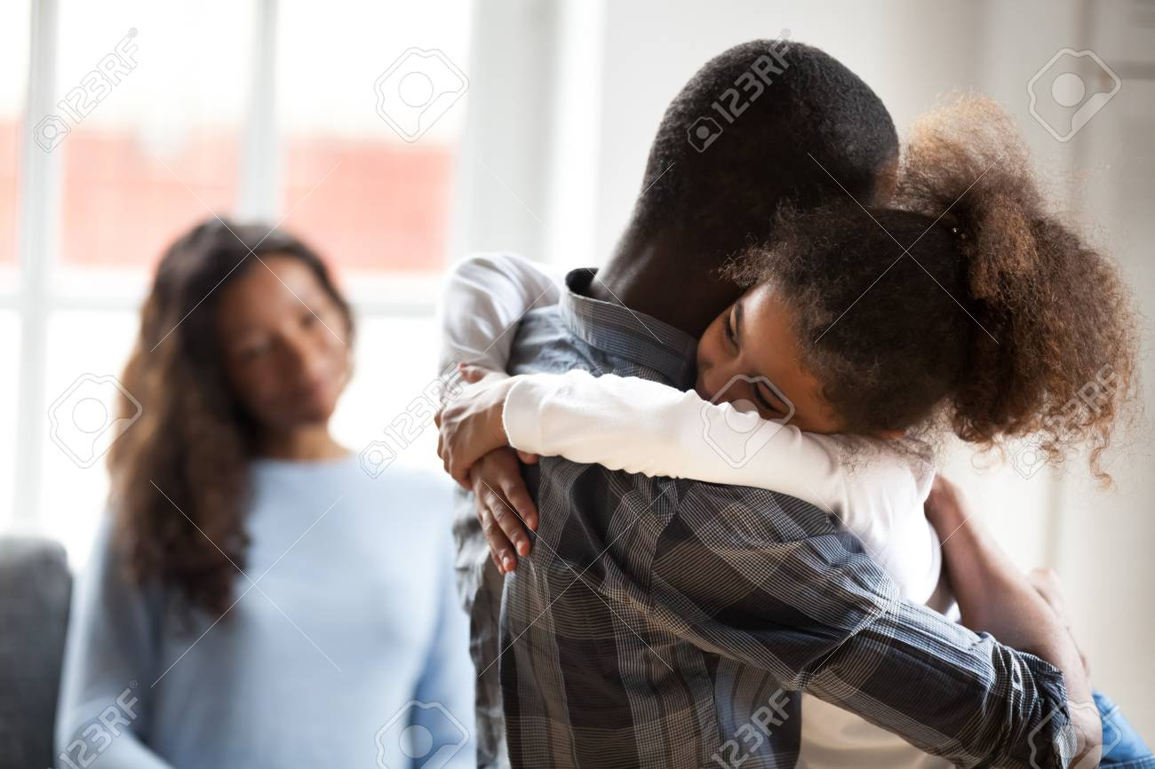Cute little preschool African American daughter hug young father showing love and care, smiling small child girl embrace black father happy to spend time with parents at home. Family wellbeing concept - 118204087