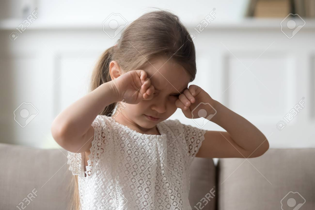 Sleepy stressed tired upset little child crying rubbing eyes feel abused hurt pain, sad lonely worried preschool kid girl in tears miss parents sitting on sofa alone, unhappy children emotion concept - 119154195