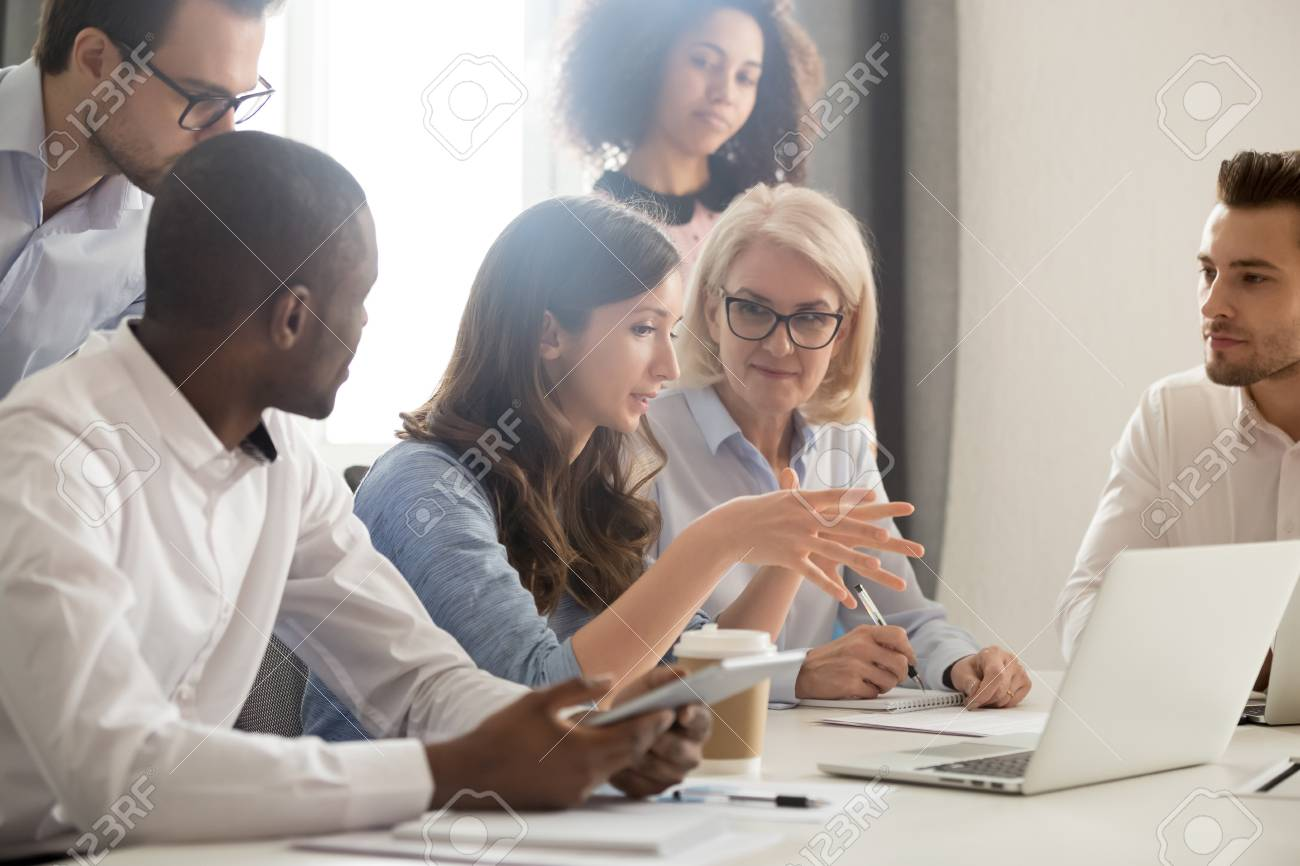Young female mentor leader coach teaching employees group analyzing online project explaining business strategy speaking training diverse corporate team with laptop using computer at office meeting. - 119154625