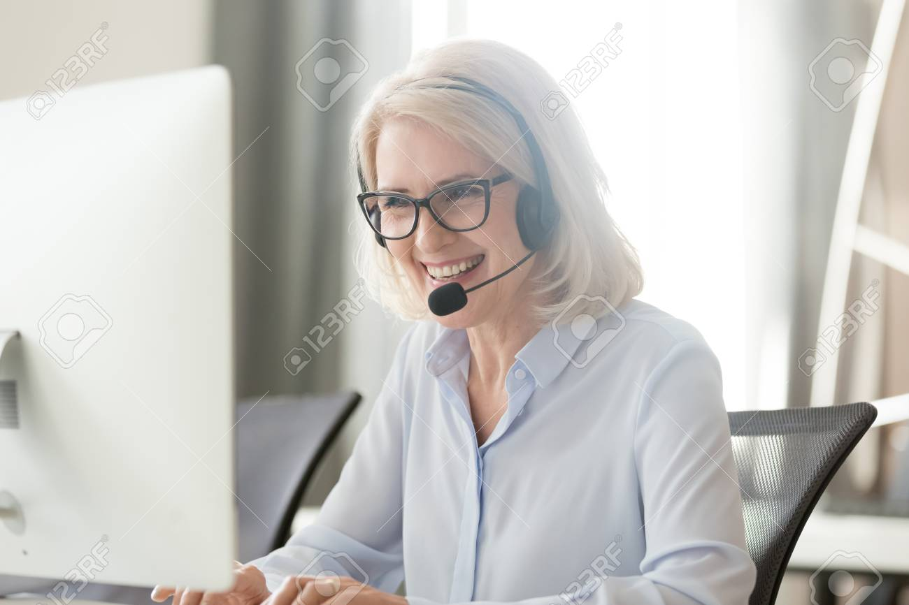 Happy old businesswoman in headset speaking by conference call looking at computer, mature female aged call center agent operator telemarketer talking consulting customer service support in office - 120519475