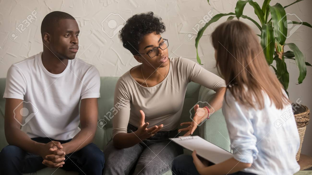Unhappy jealous mixed-race wife talk to psychologist counselor complain on bad relationship with husband, african american family couple counseling have conversation about problem at therapy session - 120572316