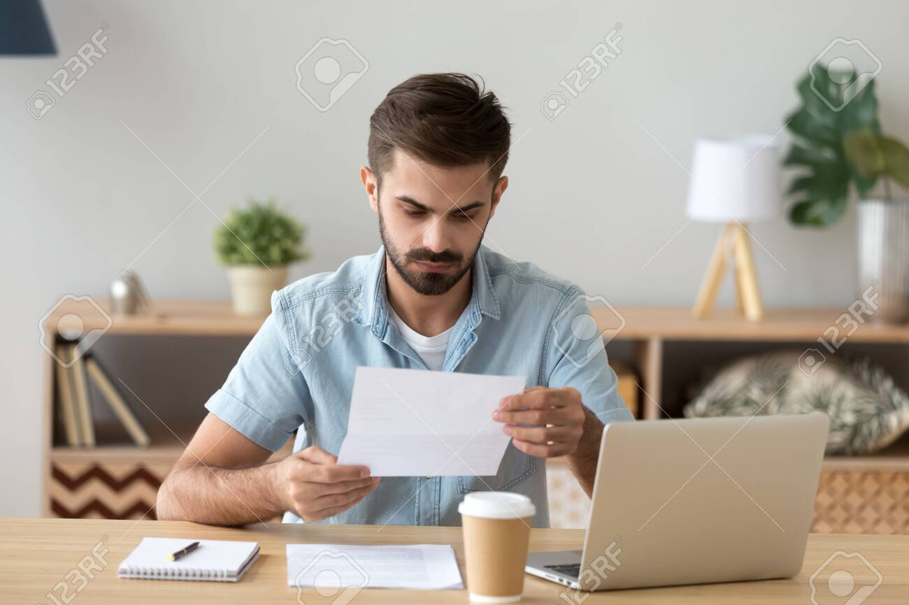 Serious focused businessman, freelancer attentively reading paper document, unpleasant news, received letter, analyzing offer, financial report with project statistics, notification - 120572617