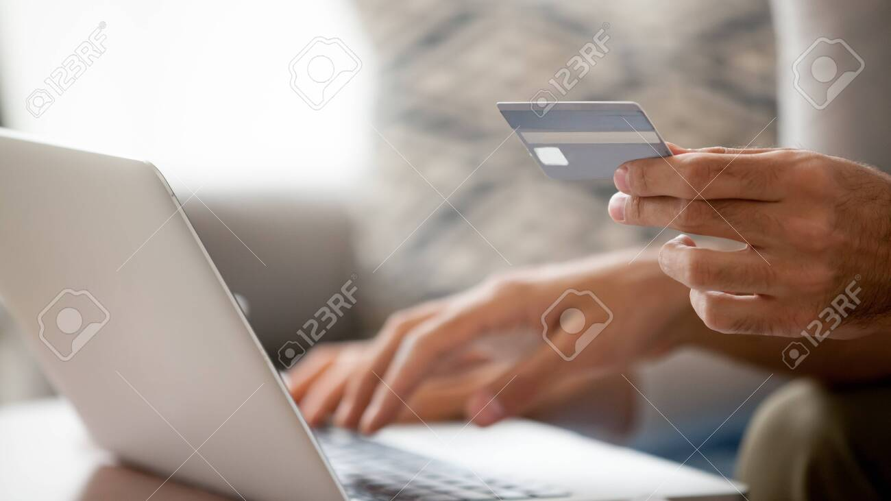 Close up man using laptop, shopping online, pay for purchases