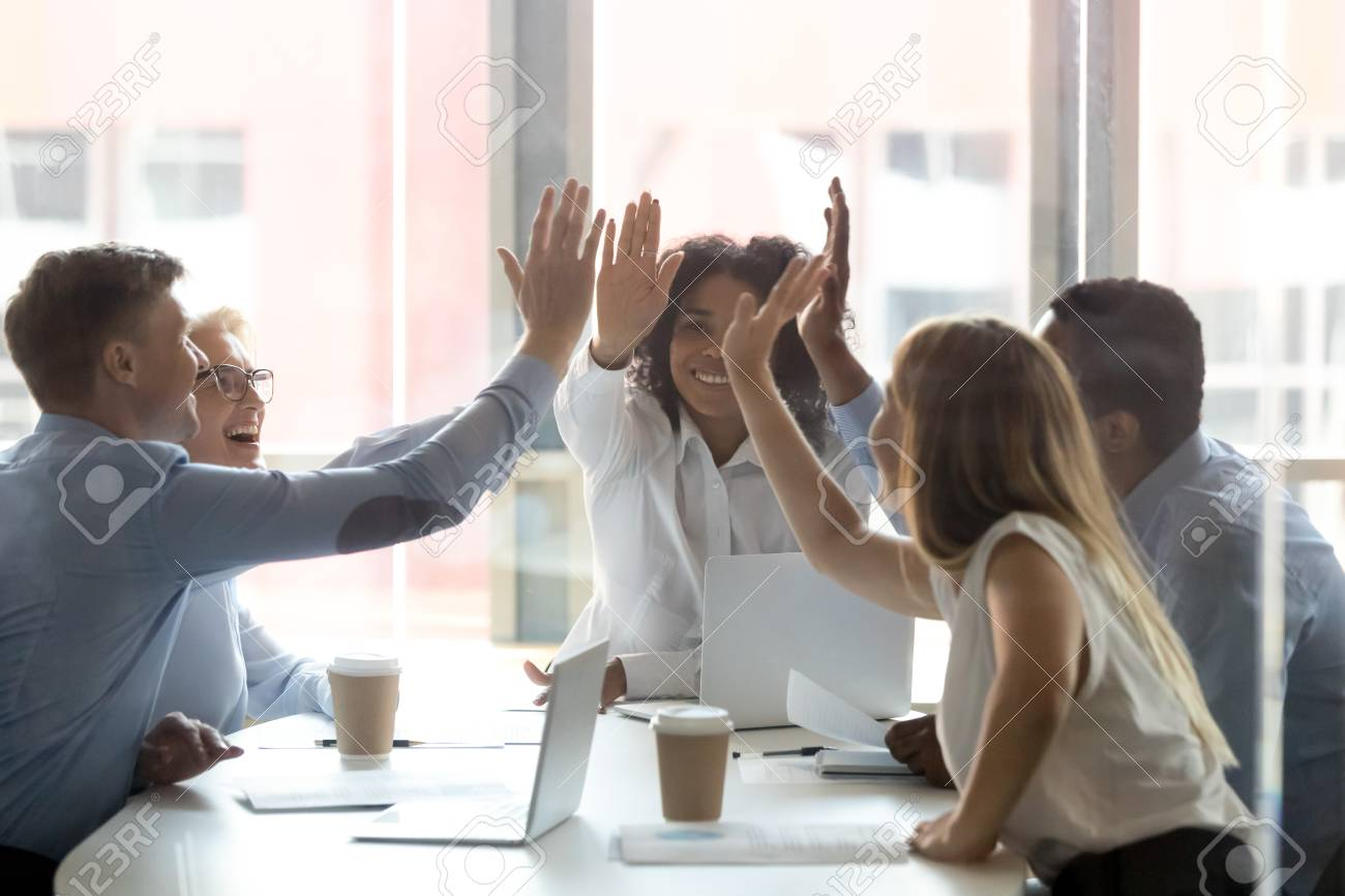 Happy multicultural executive team people give high five, diverse motivated office employees group engaged in teambuilding spirit promise trust integrity celebrate shared business success win concept - 120730155