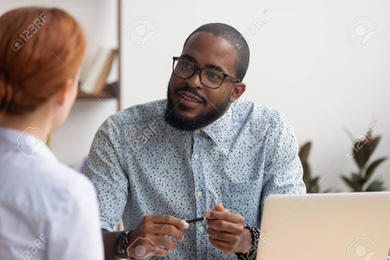 African hr manager listening to caucasian female applicant asking questions at job interview business meeting, diverse recruiter employer and seeker client talking, human resource, recruiting concept - 120839356