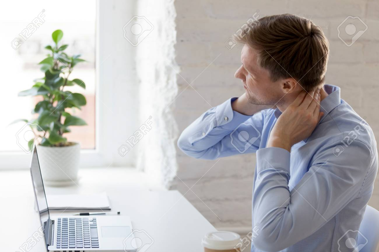 Millennial tired man having a neck pain. Male touching massaging neck sitting at workplace, suffering from discomfort long hours of sedentary life, overtime concept, muscles exhausted from overwork - 121256536