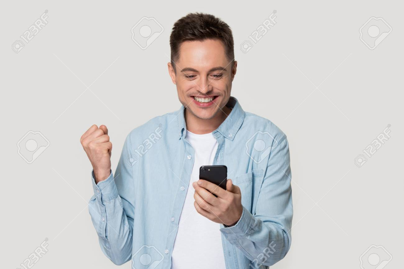 Excited Caucasian millennial man isolated on grey studio background