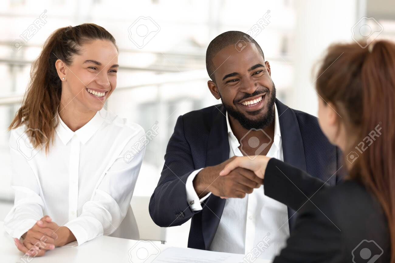 Happy mixed ethnicity couple clients handshake agents broker make agreement, african hr shake hand of caucasian candidate hiring at job interview, recruiting and insurance loan deal concept - 122245651