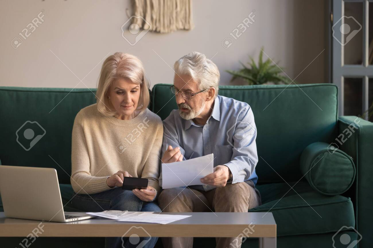 Serious mature couple calculating bills to pay, checking domestic finances, middle aged family managing, planning budget, expenses, grey haired man and woman reading bank loan documents at home - 122246949