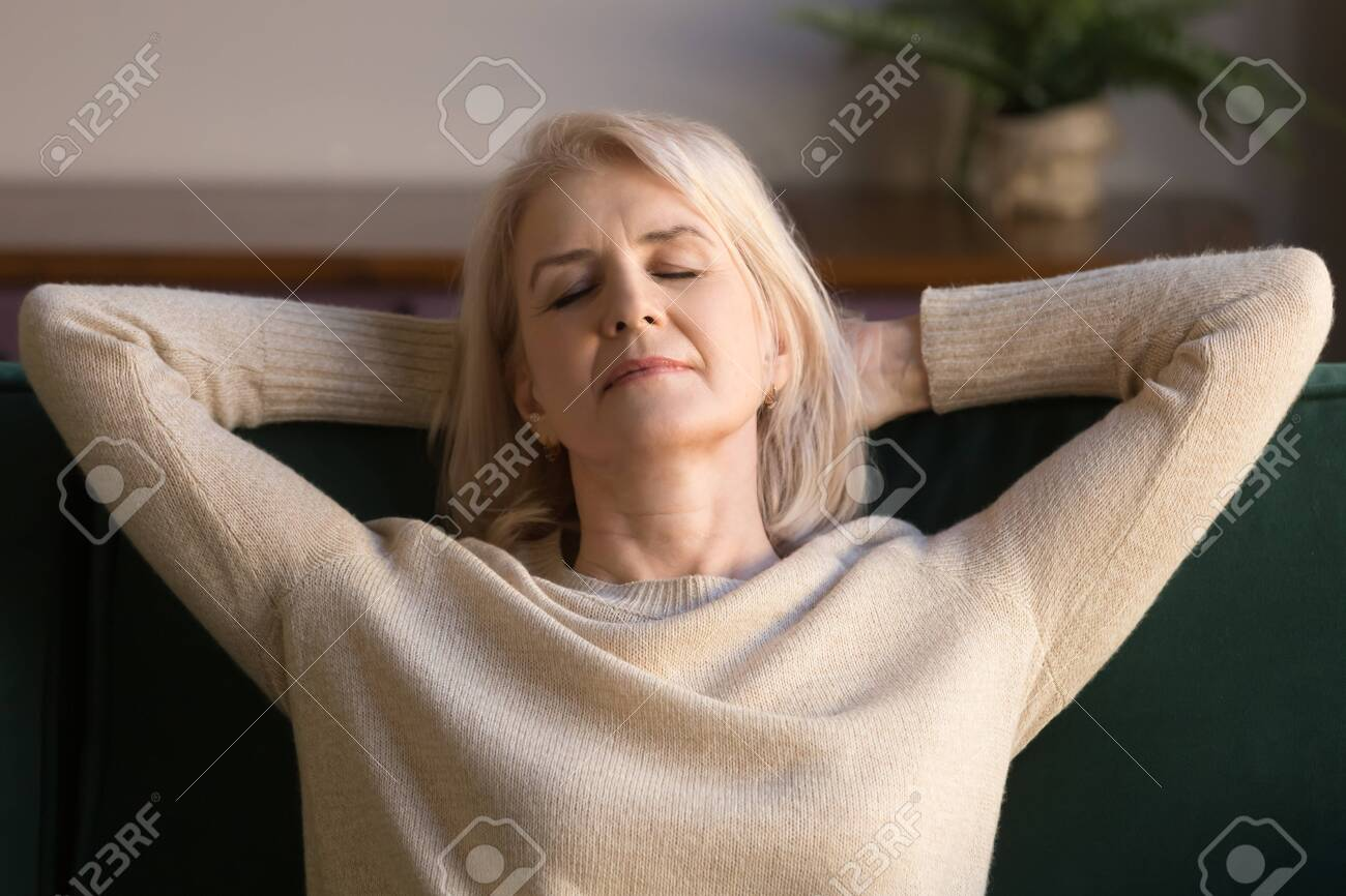 Calm middle aged woman relaxing enjoying weekend on comfortable sofa, grey haired carefree grandmother with hands behind head daydreaming, breathing, no stress peaceful free time at home close up - 122247288