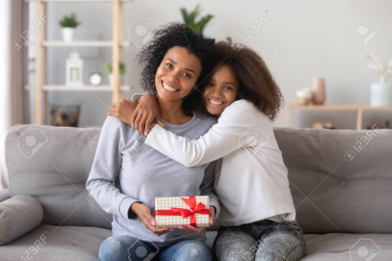 Head shot portrait of smiling African American mother received gift from teenage daughter, happy teen girl embracing mum holding box, posing for photo together, sitting on couch, looking at camera - 123628343