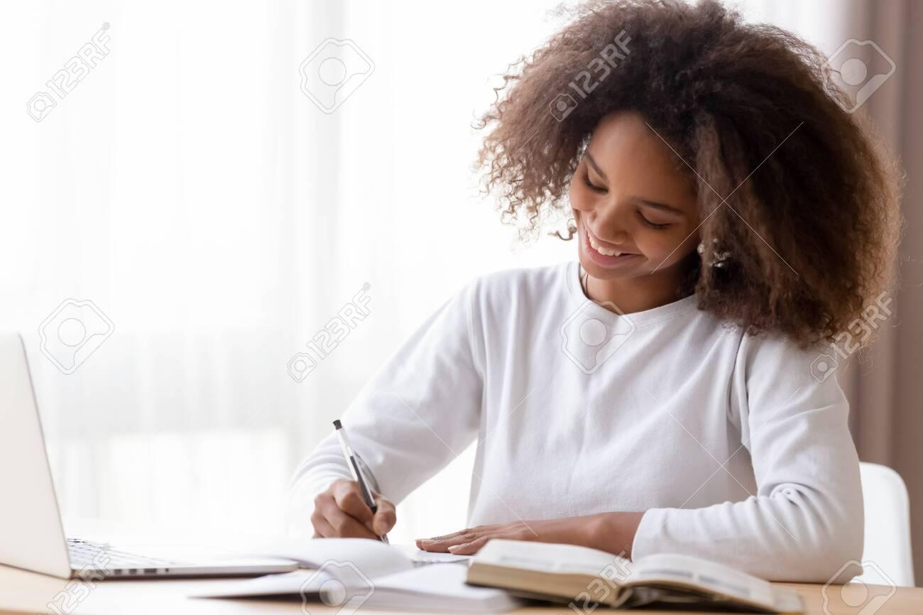 Smiling African American teen girl preparing school homework, using laptop, happy black schoolgirl, pupil doing tasks, writing essay, studying at home, making notes, writing, reading textbooks - 123628443
