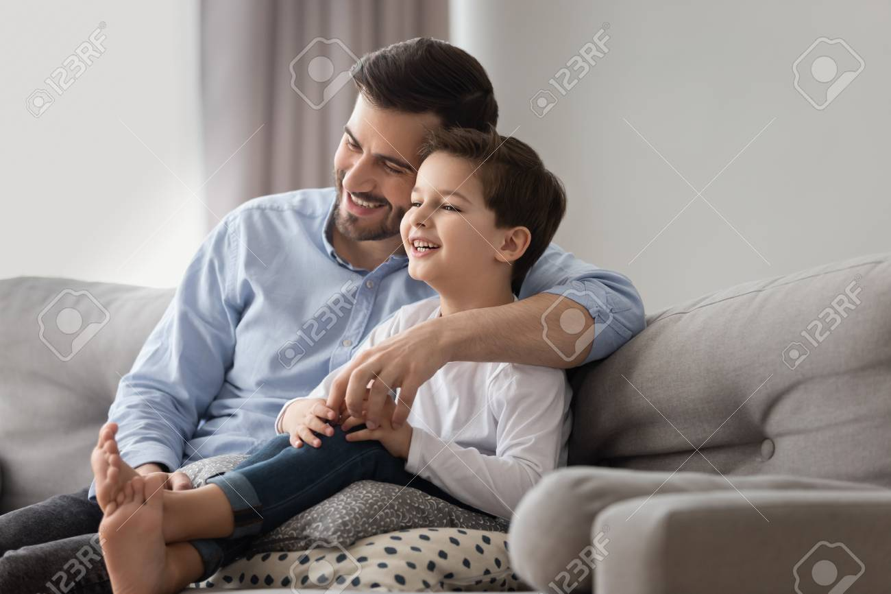 Happy Young Dad And Smiling Little Son Sit On Sofa Together Relax