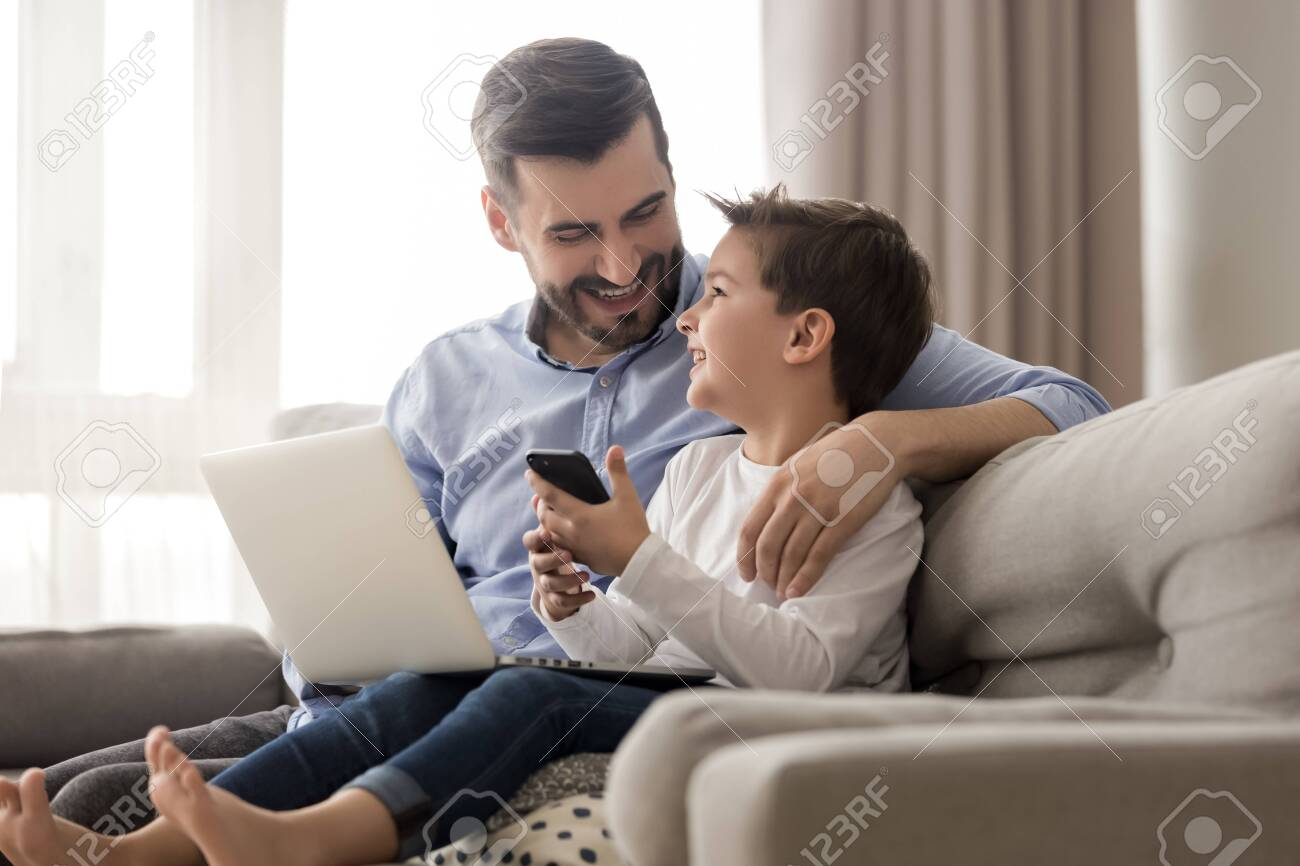 Happy young father sit on couch using laptop relax with preschooler son holding smartphone have fun together, smiling dad and little boy child enjoy weekend at home rest on sofa busy with gadgets - 123628553