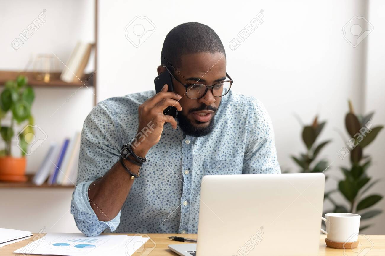 Serious african-american employee making business call focused on laptop at workplace. Black businessman consulting customer, discussing financial report. Contract negotiation and discussion concept - 124259884