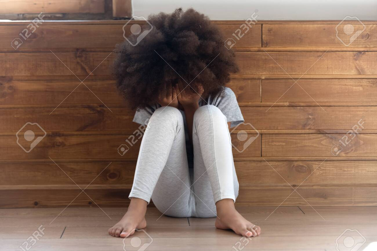 Sad stressed little african american girl crying, upset lonely bullied child feels abandoned abused, preschool black orphan kid in tears sit alone on floor, children abuse, unhappy childhood concept - 124264244