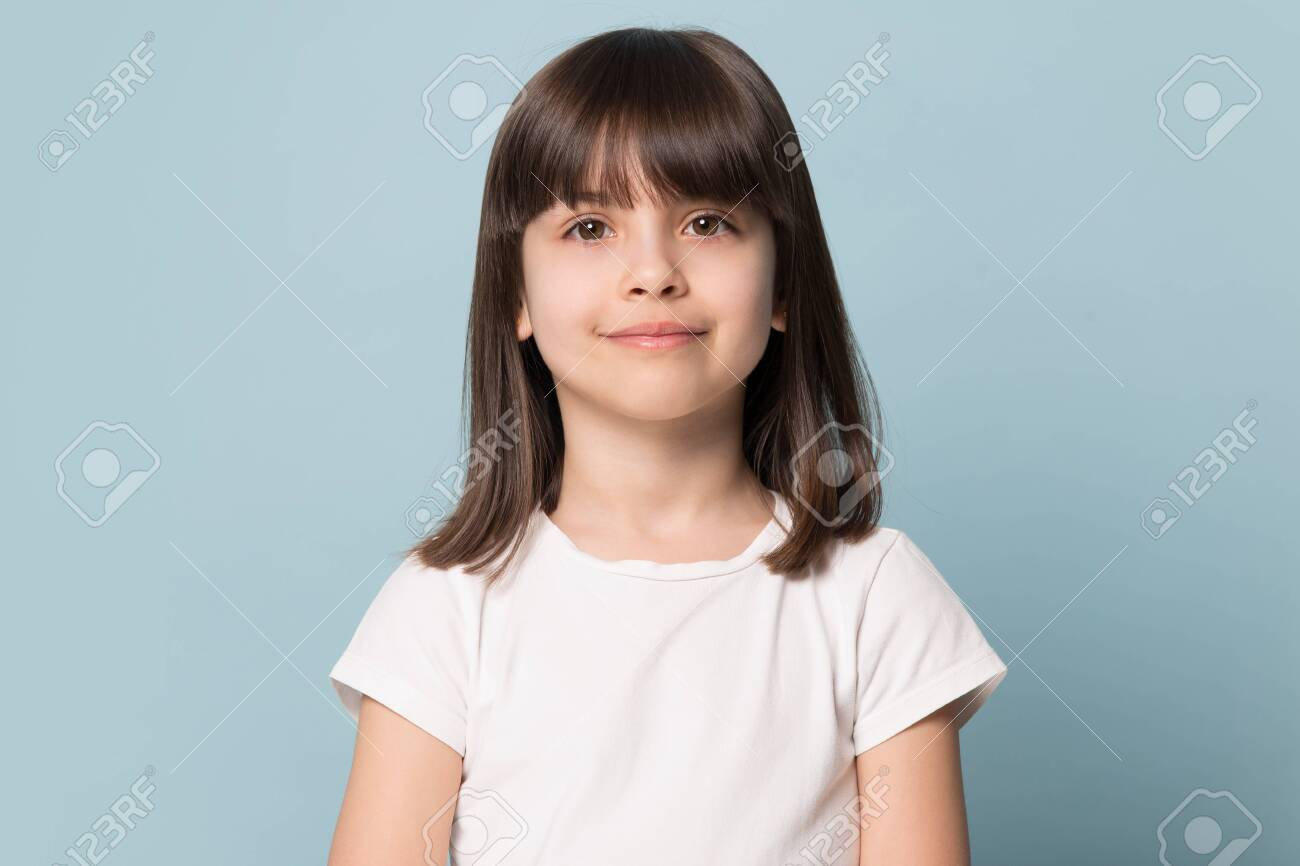 Adorable six years old girl in white t-shirt isolated on blue studio background, pretty brown-haired fringe hairstyle european appearance child pose indoor smiling look at camera, generation Z concept - 124555005