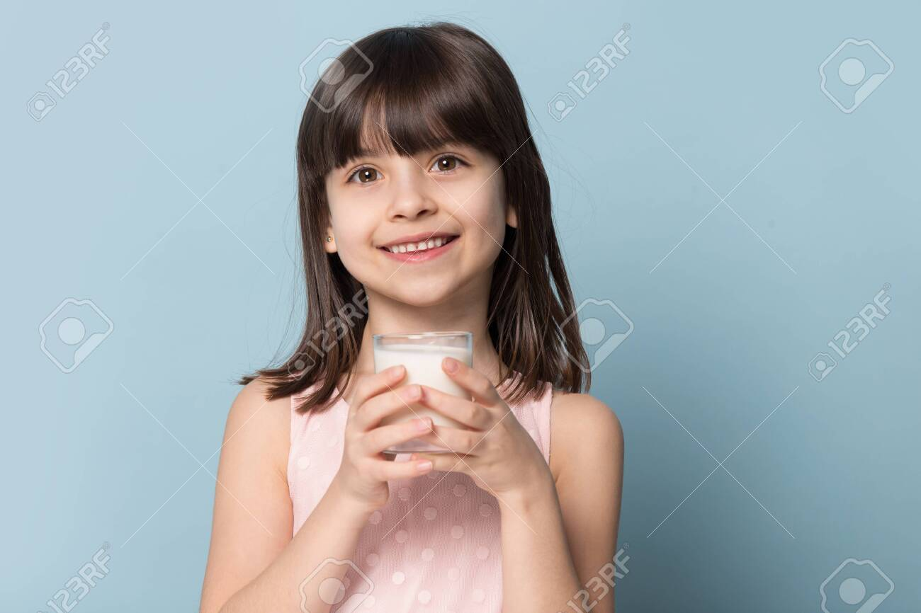 Preschool girl brown-haired adorable kid holds glass with milk source of protein, calcium and vitamin D, smiling looking at camera isolated on blue studio background, healthy habits lifestyle concept - 124555031