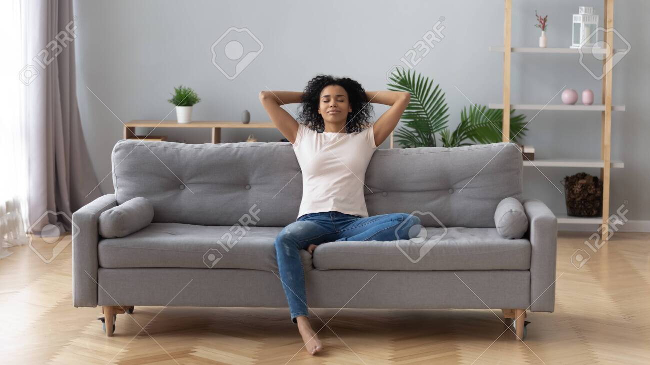 Young calm black woman relaxing sit on comfortable sofa in modern..