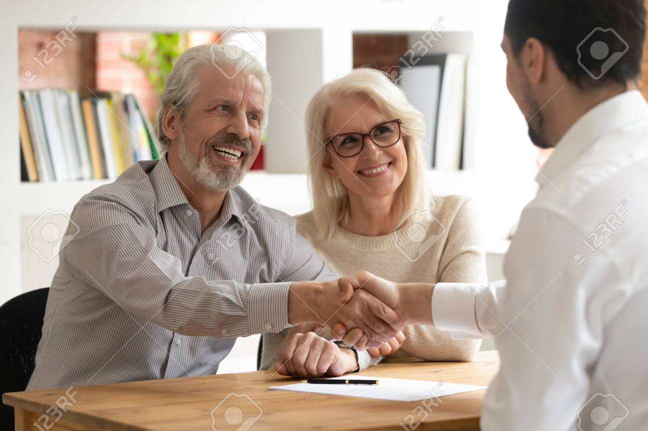 Happy senior old family couple clients make financial insurance estate business deal handshake agent lawyer, satisfied mature customers shake hand meeting bank manager agree on investment contract - 126490052