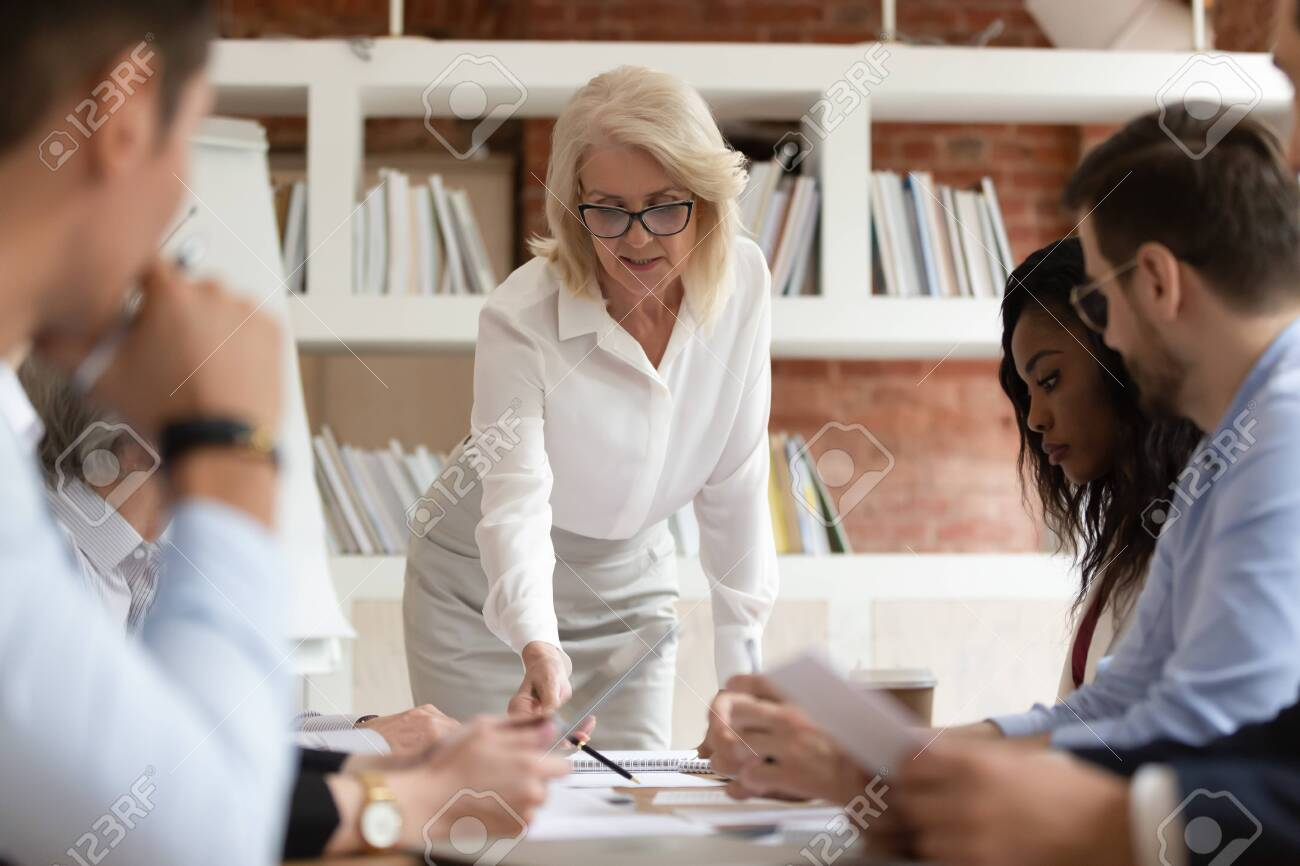 Focused diverse business executive team people with old middle aged boss manager discuss paperwork at group meeting, senior mature female leader presenting financial report work plan at briefing - 126490160