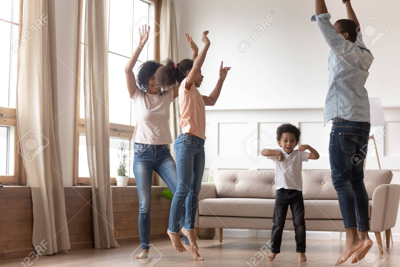 Joyful Happy African Family Having Fun Jumping In Living Room