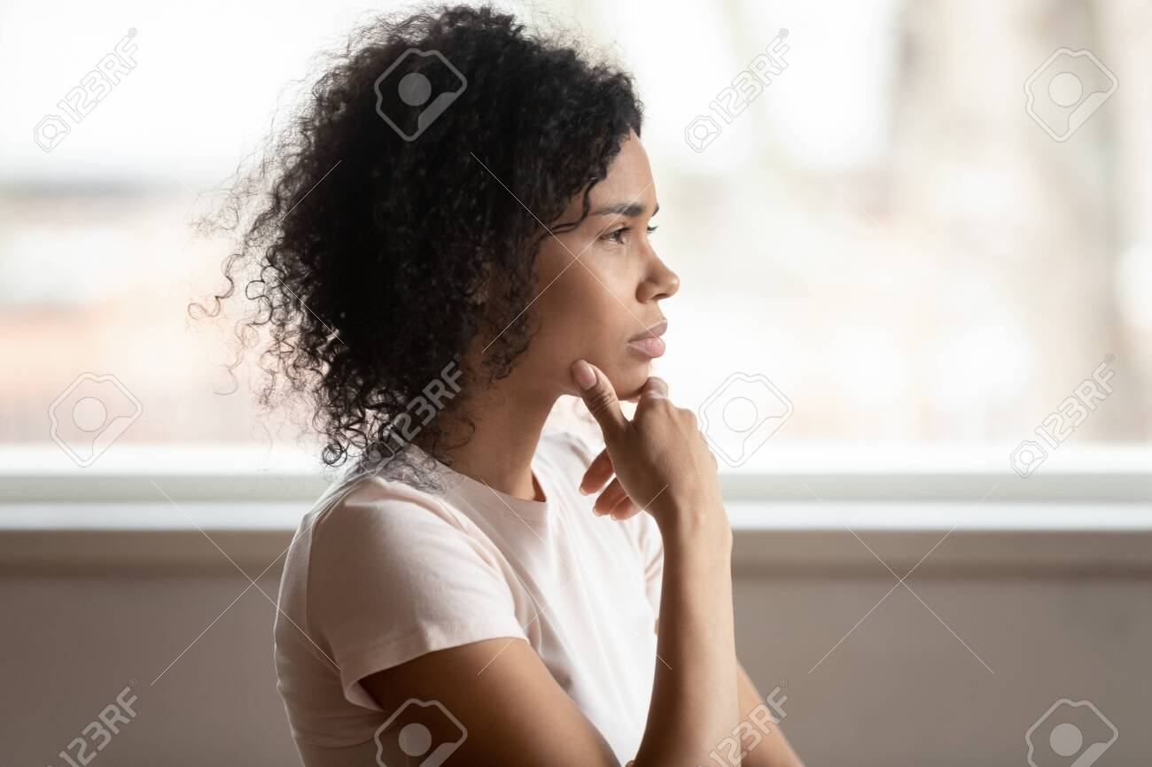 Pensive mixed race 30s woman sitting at home touch chin lost on deep thoughts thinking makes decision, side view face, challenge, problems solution, solving issues, consideration or brain work concept - 127893968