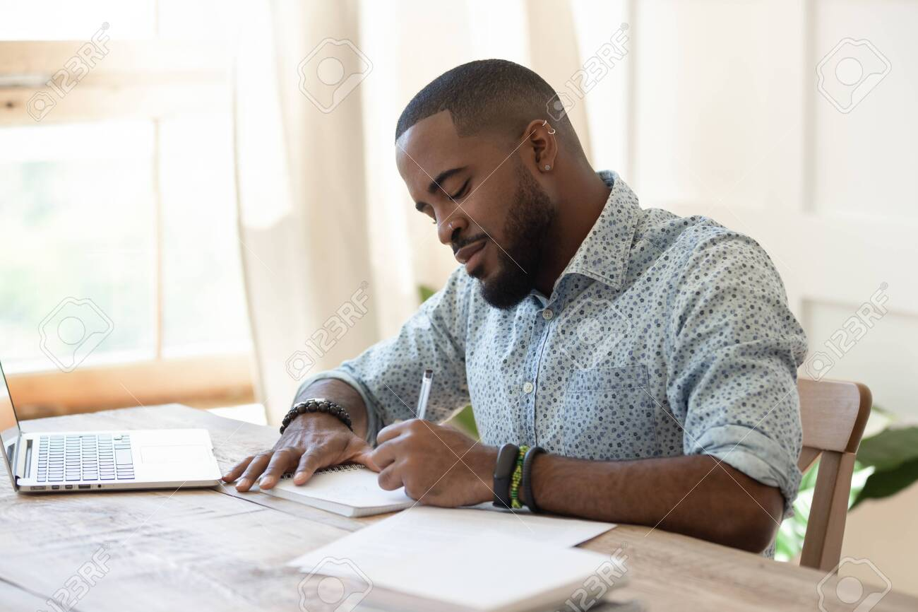 Focused african american man student freelancer making notes studying working with laptop, young black man professional writing essay in notebook preparing for test exam sit at home office desk - 128112743
