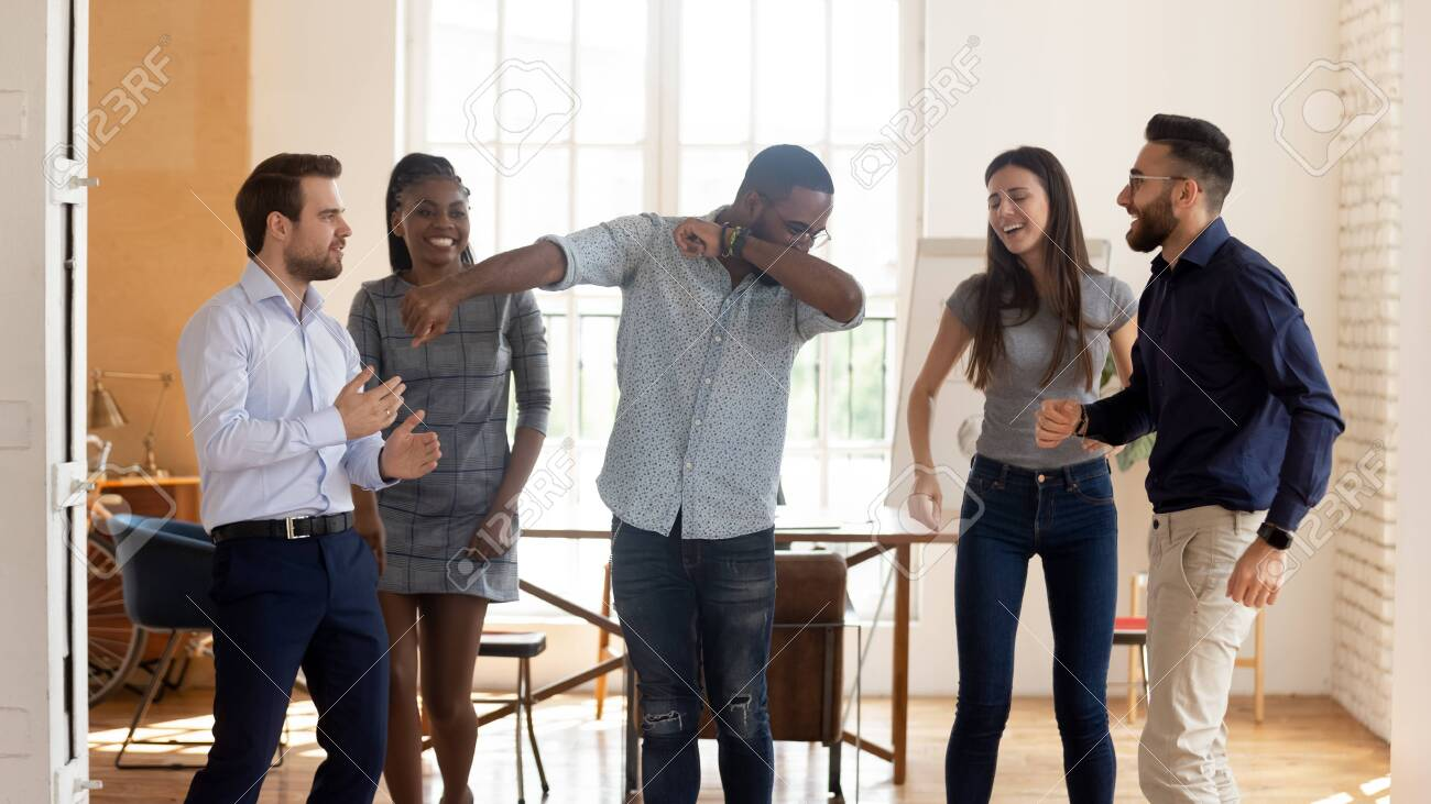 Happy funny motivated diverse business team people celebrating success win or enjoying corporate party in victory dance, positive friendly multiracial coworkers dancing in office having fun together - 129153013