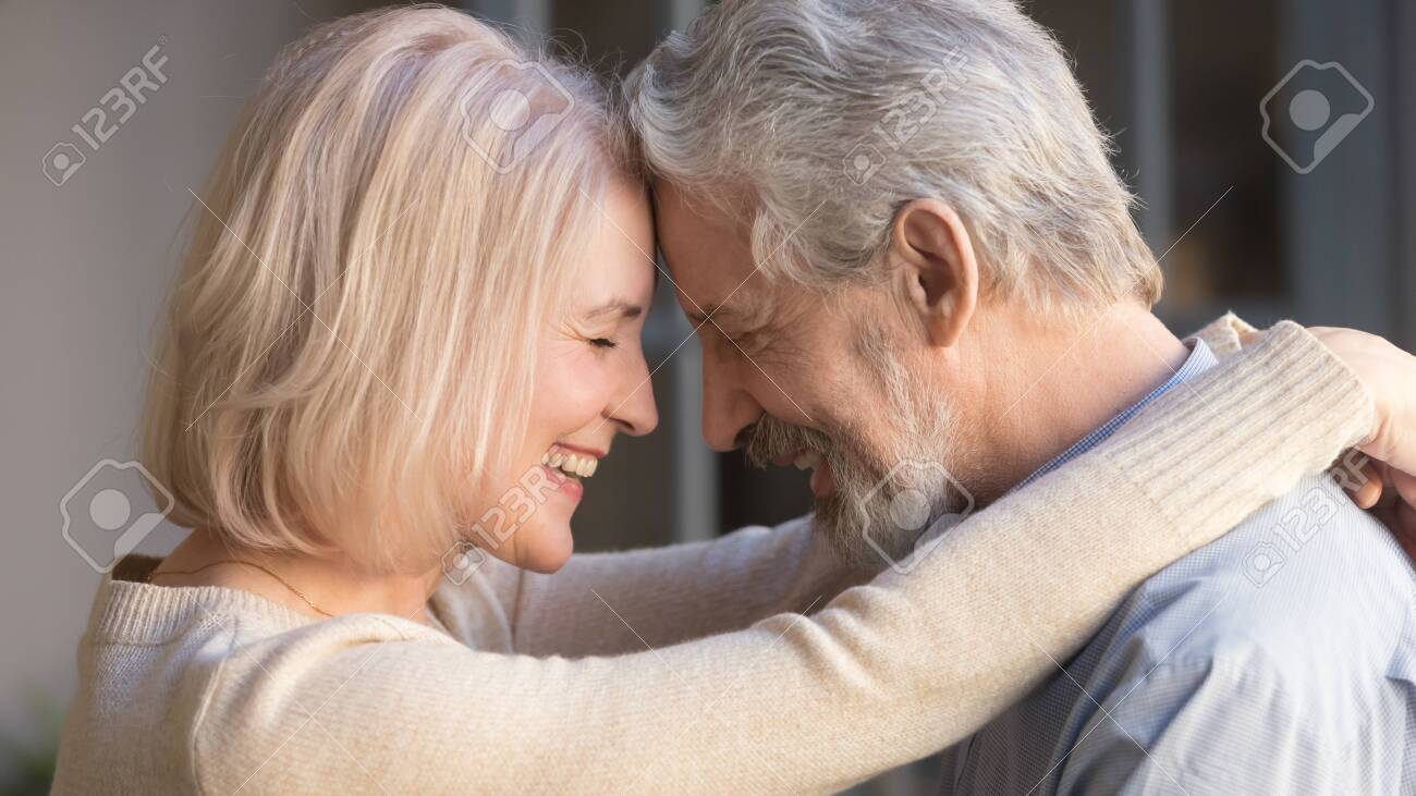 Loving old senior family couple bonding embracing touching foreheads, romantic middle aged mature man and woman hugging getting closer enjoying moment of affection cuddling, close up side view - 129116204