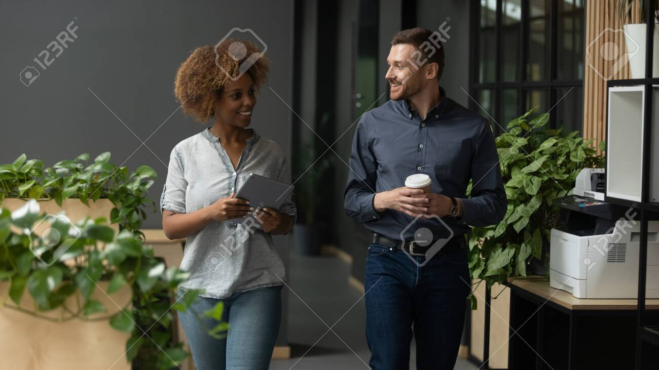 Two diverse professional colleagues talking walking in modern office, happy friendly african female and caucasian male coworkers having conversation discuss project going along business work space - 129469752