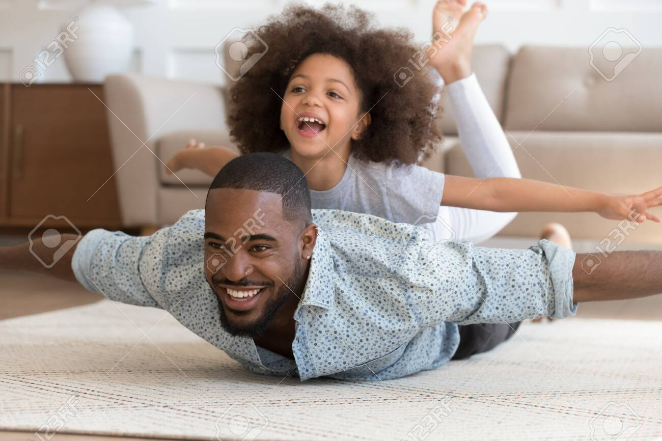 Happy african american dad lying on floor carpet with cute daughter on back, pretending to be planes. Overjoyed smiling girl enjoying weekend time with daddy, playing, laughing. Active family leisure. - 129451036