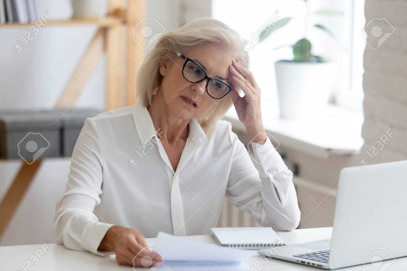 Pensive aged businesswoman in glasses sit at office desk thinking of problem solution, thoughtful senior woman worker in glasses look at laptop screen hold document pondering or making decision - 129607102