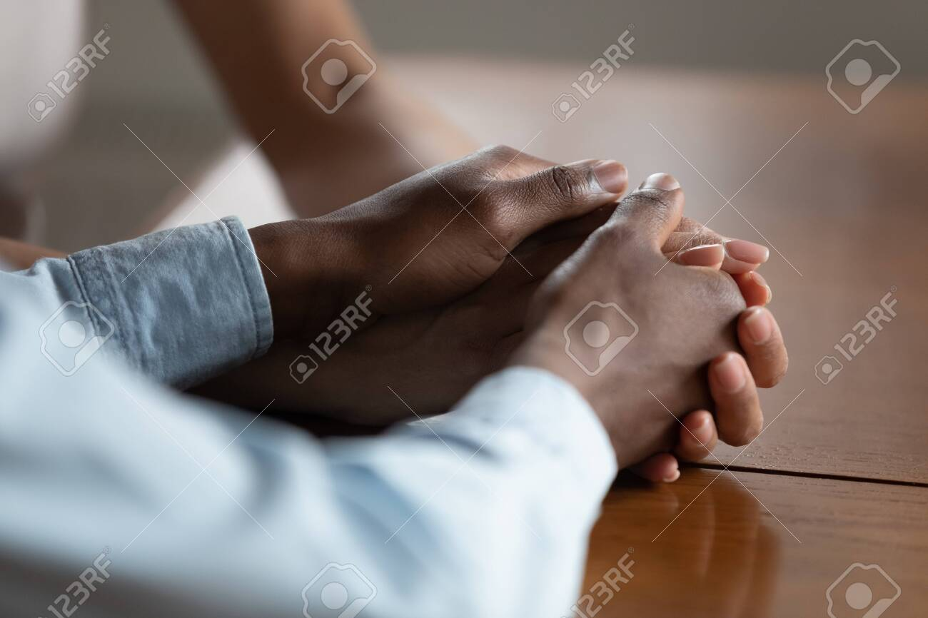 Close up of african American couple hold hands on wooden table make peace reconcile after fight, biracial husband and wife show love, care and support, have romantic intimate moment. Devotion concept - 129610676