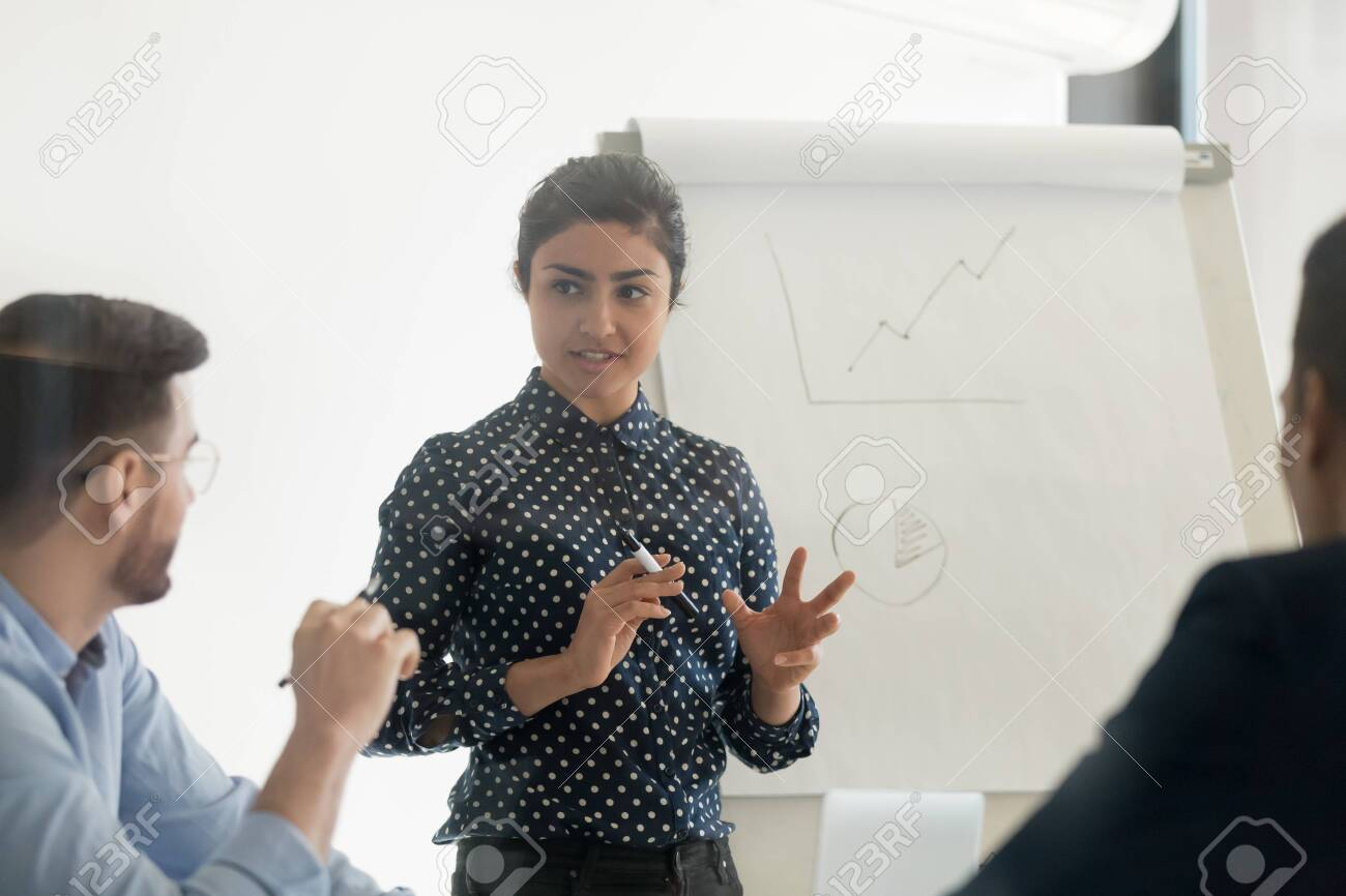 Confident female indian conference speaker coach training diverse employees group give flip chart presentation at office meeting, hindu business woman presenter teach staff team at corporate workshop - 131244726