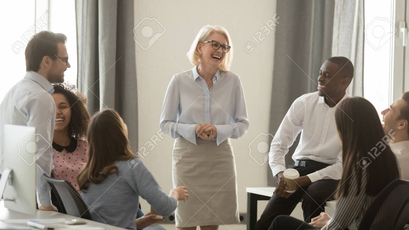Laughing old coach team leader talking with diverse coworkers chatting at business meeting, friendly multi racial office workers and middle aged woman ceo have fun conversation at coffee break concept - 131842628