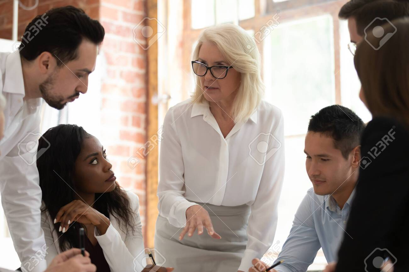 Motivated multiracial businesspeople gather talking discussing business project at company meeting, successful diverse employees colleagues collaborating together at briefing brainstorming over ideas - 131272245