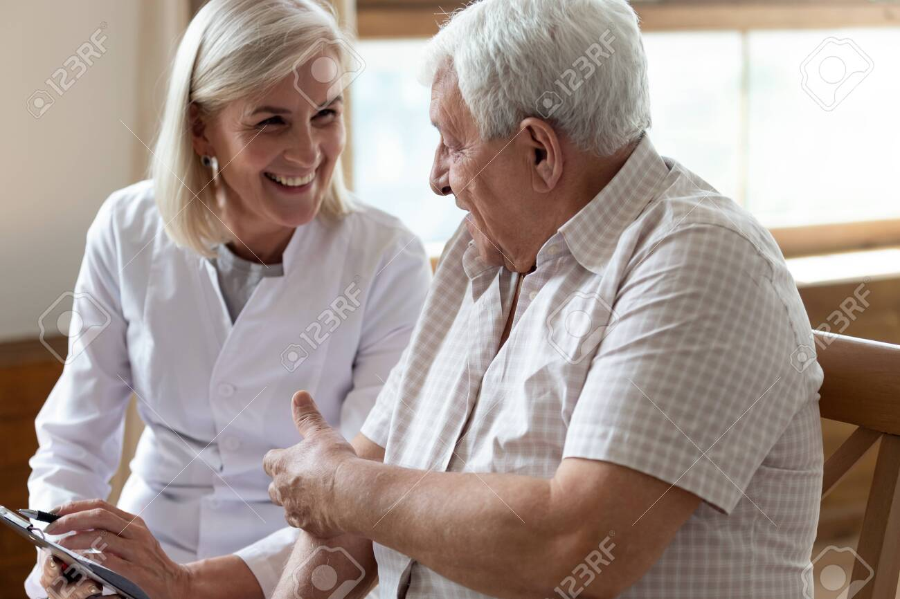 Elderly 80s man patient and middle-aged nurse medical worker holding clipboard writing personal information having pleasant warm conversation talk with clinic client nursing caregiving service concept - 131399177