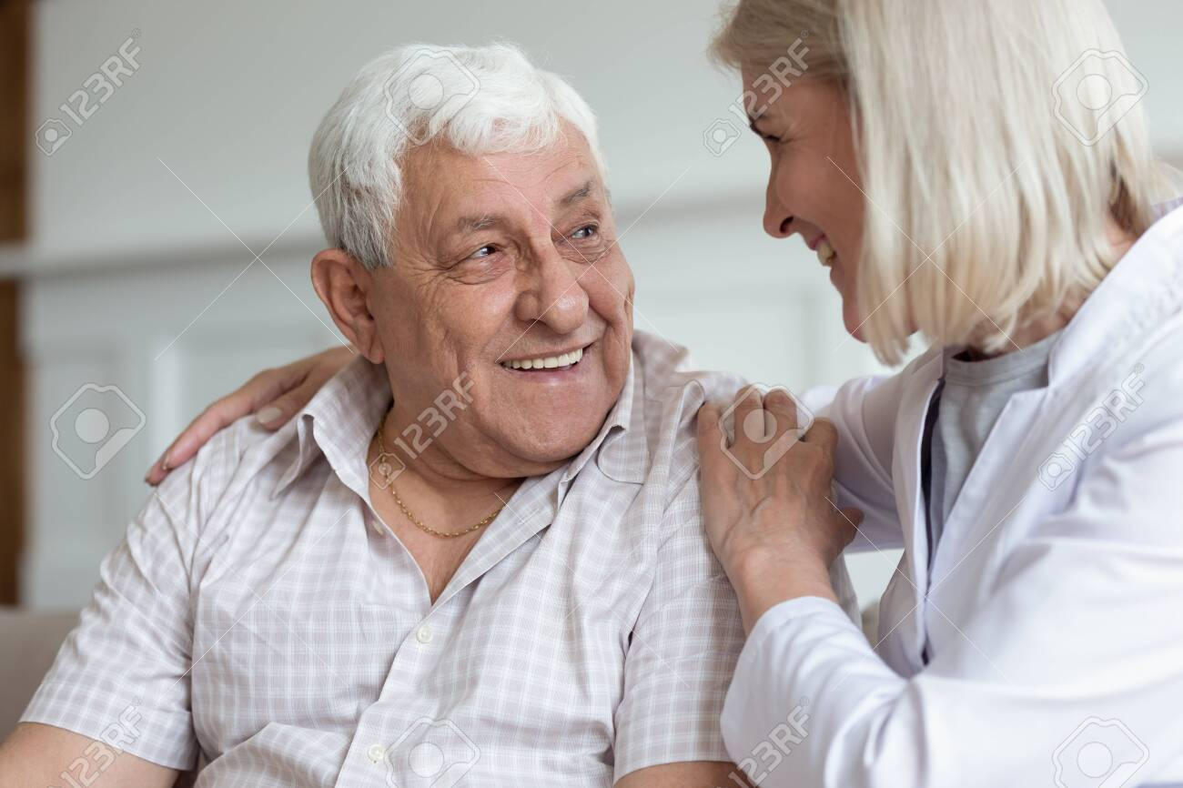 Middle-aged nurse hug elderly man patient sitting on couch look at each other having warm relations understating. Concept of caregiving solve problems together helping give mental or physical support - 131665040