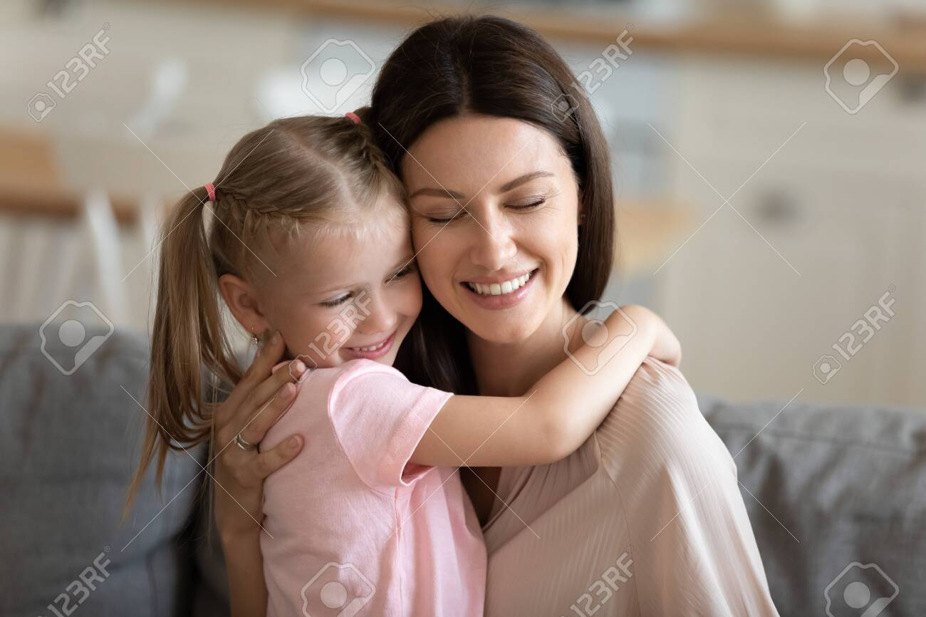Happy loving mother embracing little daughter close up, enjoying free time together at home, smiling mum and adorable preschool child hugging and cuddling with closed eyes, trusted good relationship - 131415160