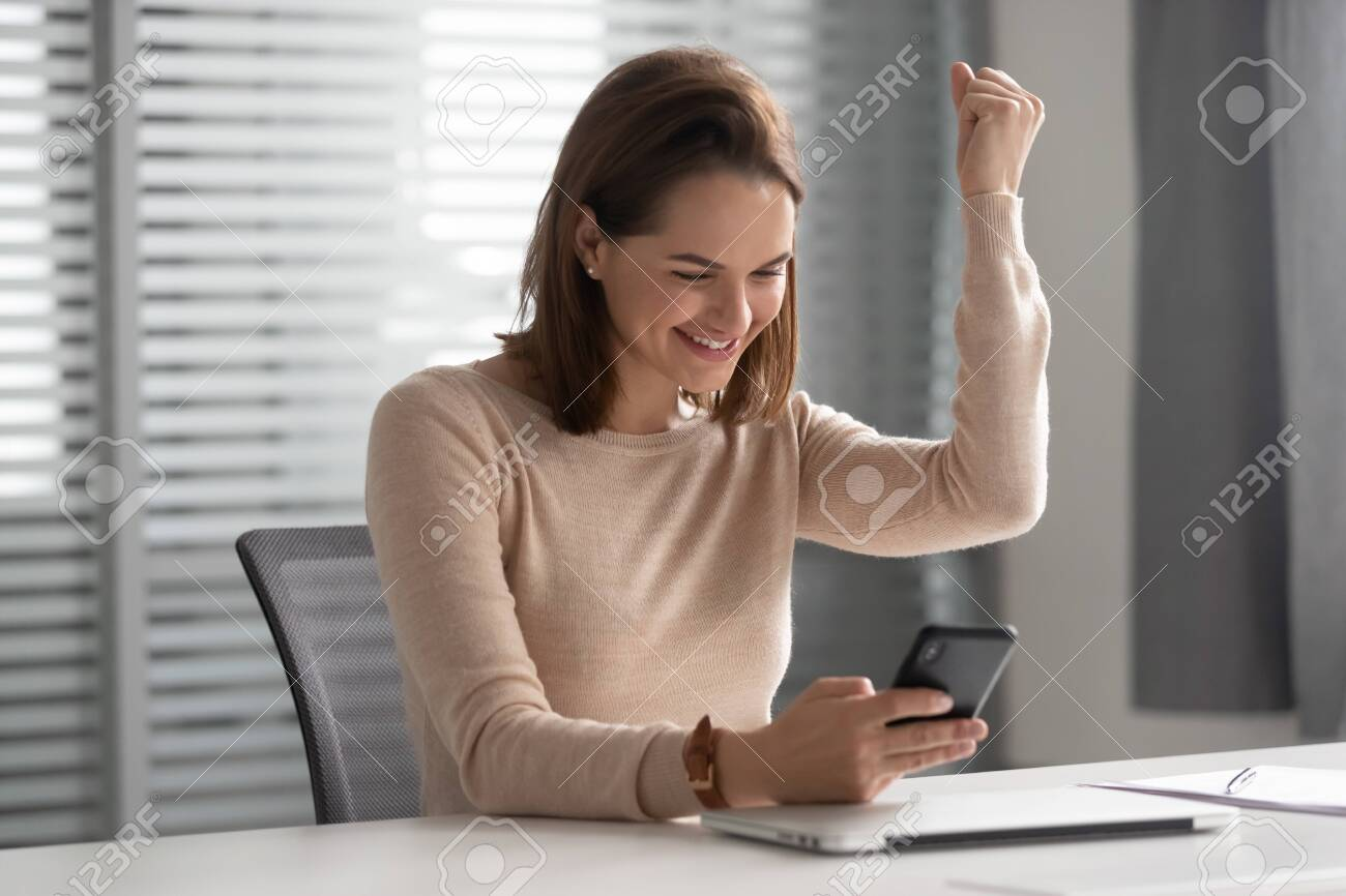 Happy smiling businesswoman using cellphone, excited female employee celebrating success, win, reading good news in email message, looking at phone screen, positive exam results, promotion - 131735524