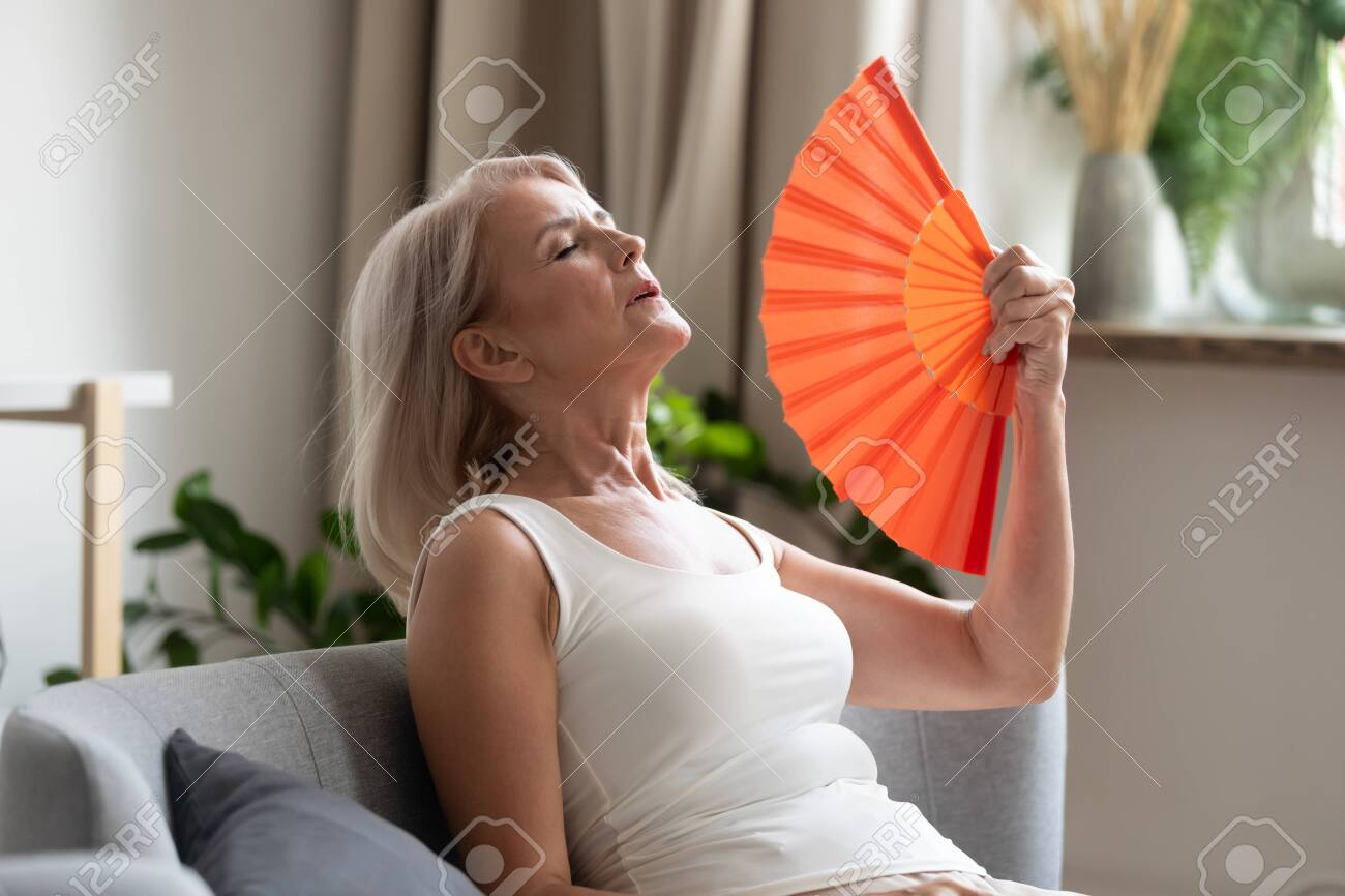 Stressed annoyed old senior woman using waving fan suffer from overheating, summer heat health hormone problem, no air conditioner at home sit on sofa feel exhaustion dehydration heatstroke concept - 132157358