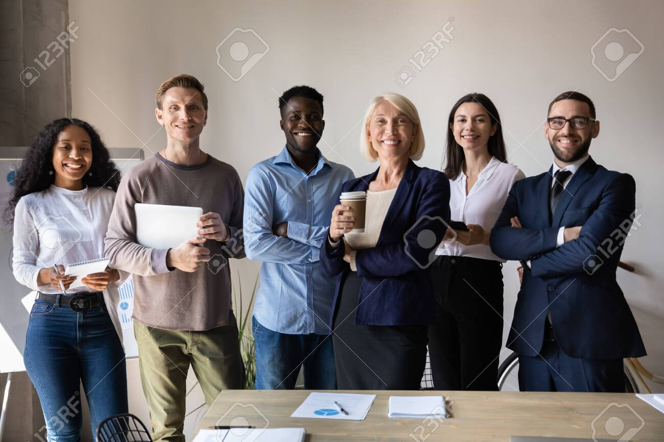 Happy confident diverse old and young business people stand together in office, smiling multiethnic professional colleagues staff group look at camera, human resource concept, team corporate portrait - 132157592