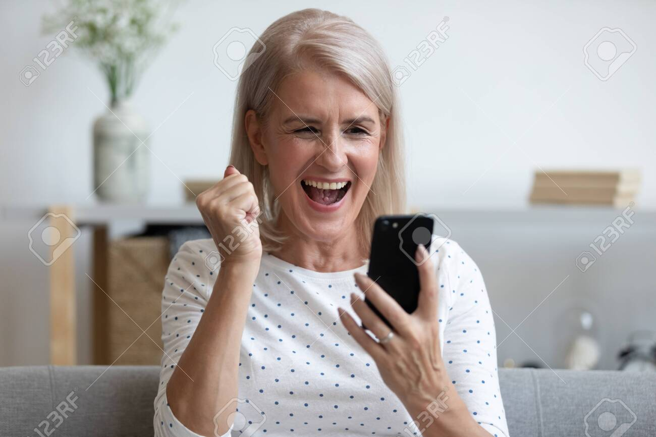Overjoyed mature old woman hold phone looking at screen feel excited about mobile online app bid win, happy middle aged lady winner celebrate victory success read message good news in cell at home - 132280537