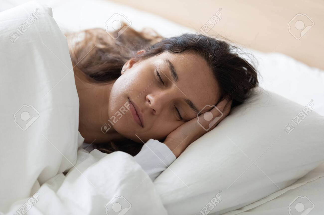Head shot close up side view tranquil young biracial woman lying in bed, covered with fresh linen, enjoying lazy weekend time. Pretty girl relaxing with closed eyes, feeling peaceful at home. - 132120554