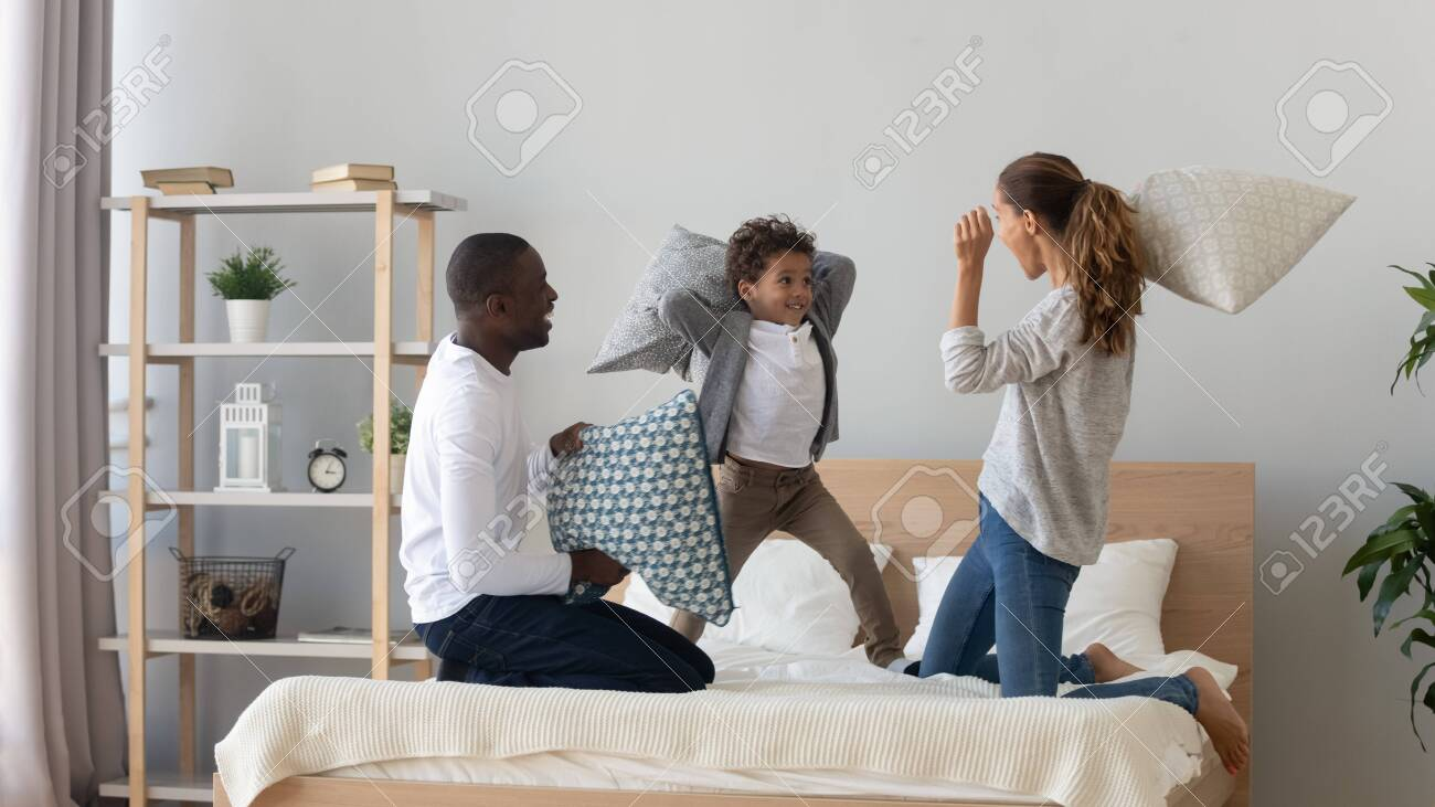Excited multiracial young family with little boy child have fun in bedroom engaged in pillow fight, overjoyed happy international mom and dad play with small son, enjoy weekend at home together - 132461931