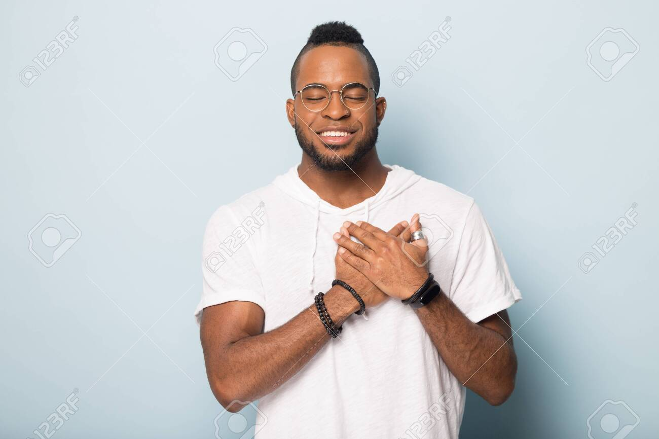 Smiling calm african American man in glasses isolated on blue studio background hold hands at heart chest praying, grateful biracial male believer feel happy peaceful, thanking god, faith concept - 132399752