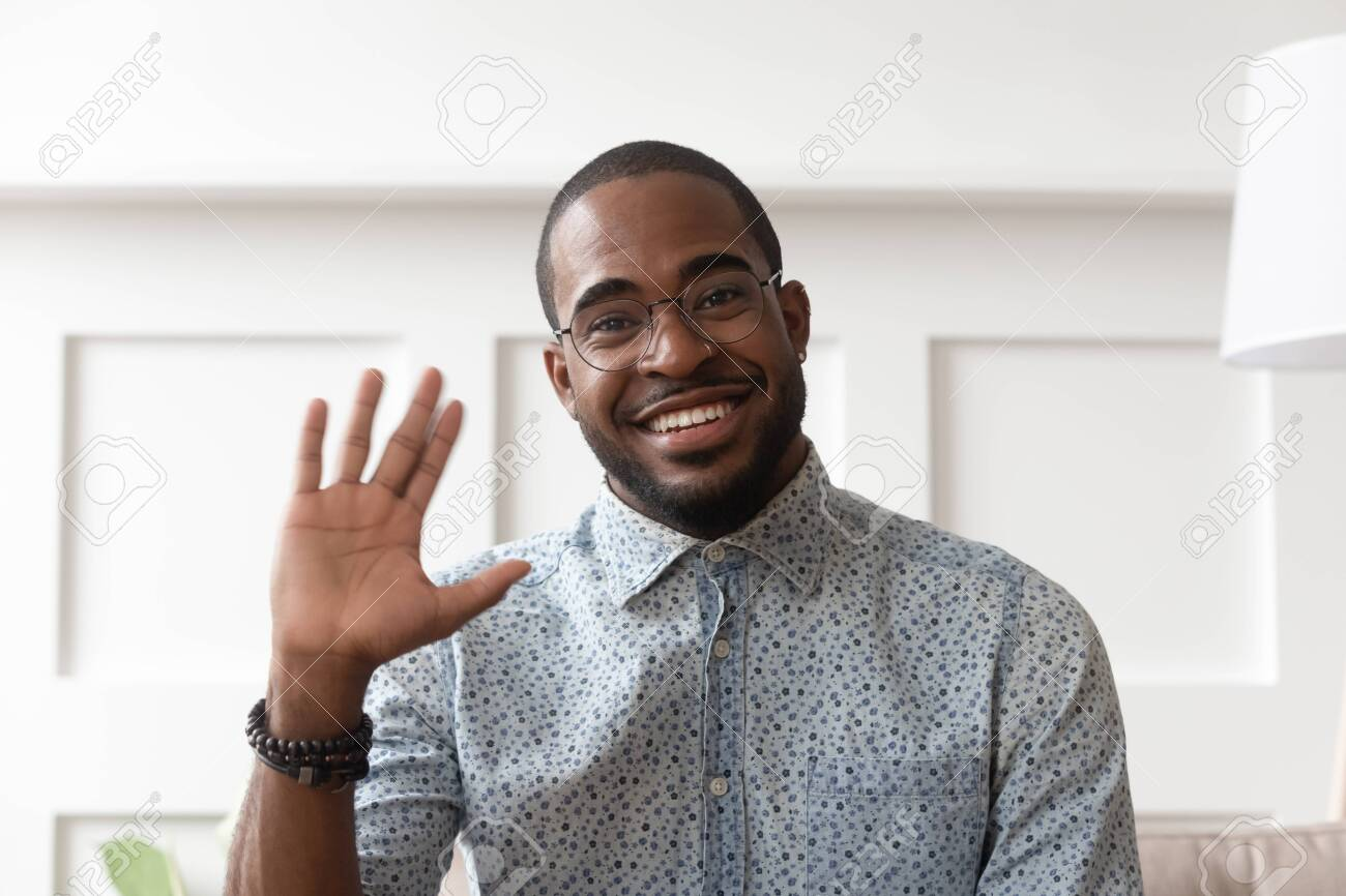 Smiling african American millennial man in glasses look at camera waving saying hello talking on video call, happy black male vlogger in spectacles greeting with subscribers shooting video blog - 132462825