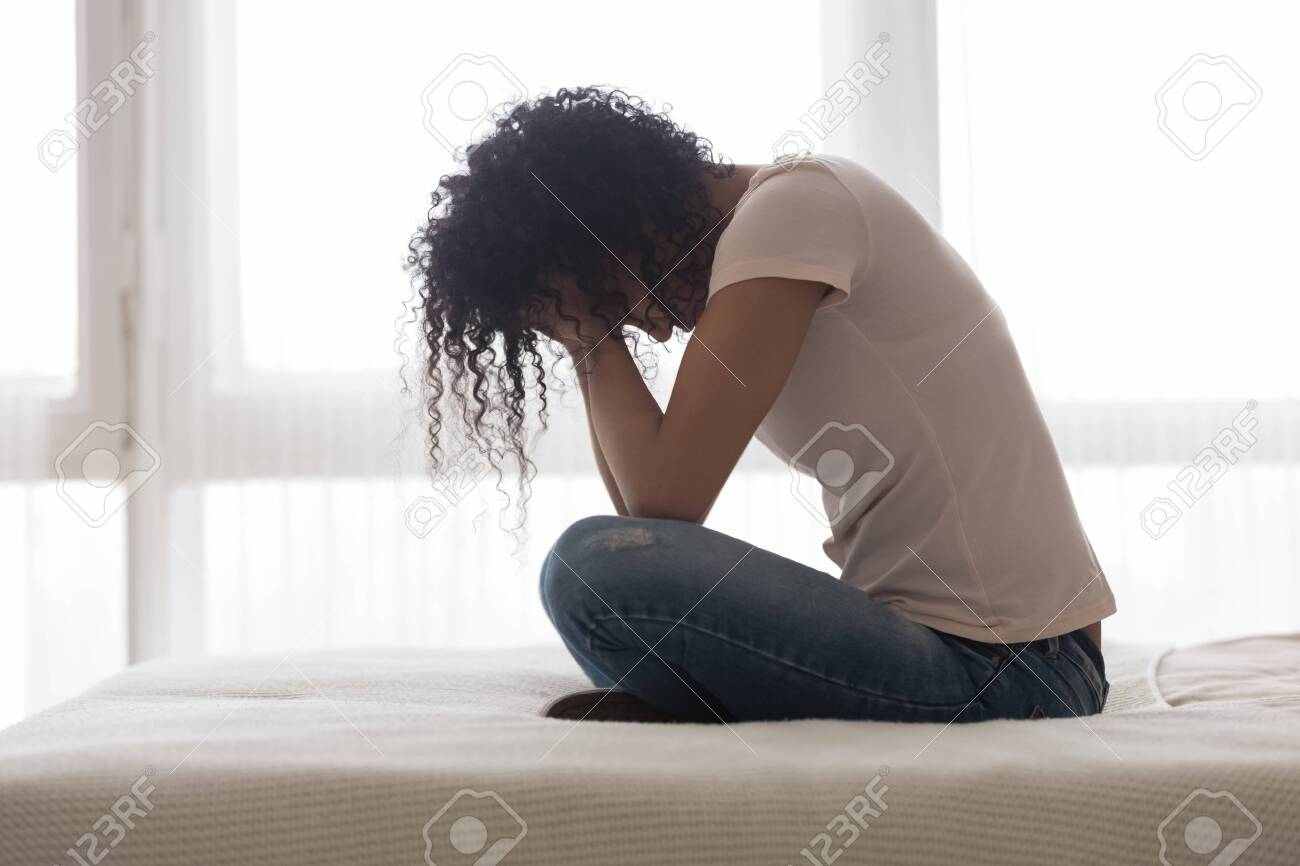 Upset sad African American woman suffering from loneliness side view, sitting in bed alone, holding head in hands, upset girl has psychological troubles, trauma, thinking about problem in bedroom - 133472934